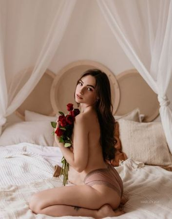 Innocent cute camgirl sitting in her bed while holding a bouquet of roses and looking in camera