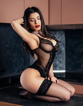 Hot cam model with perfect body sitting on her kitchen while wearing the best lingerie set ever